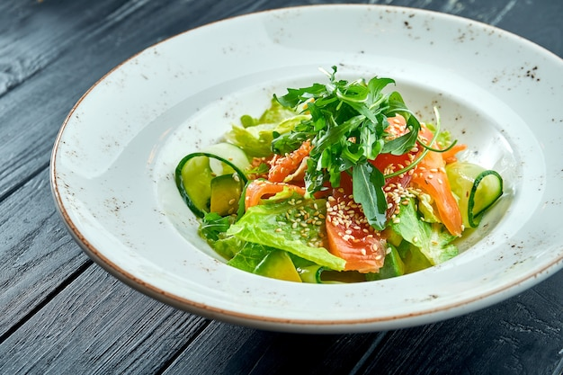 Apetyczna, dietetyczna sałatka z sałatą, ogórkiem, awokado i lekko solonym łososiem w białym talerzu na ciemnej powierzchni drewna. zdrowe jedzenie