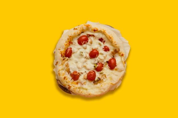 Apetyczna domowa pizza z serem i pomidorami na żółtym tle z copyspace