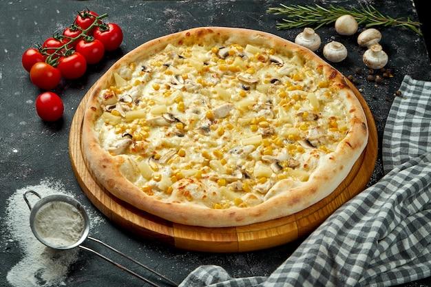 Apetyczna hawajska pizza z kurczakiem, grzybami, kukurydzą i ananasami w kompozycji ze składnikami na czarnym stole