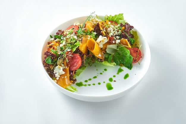 Apetyczna i dietetyczna sałatka z pieczonej dyni, rukoli, fety i pomidorów w białej płytce na białym tle.