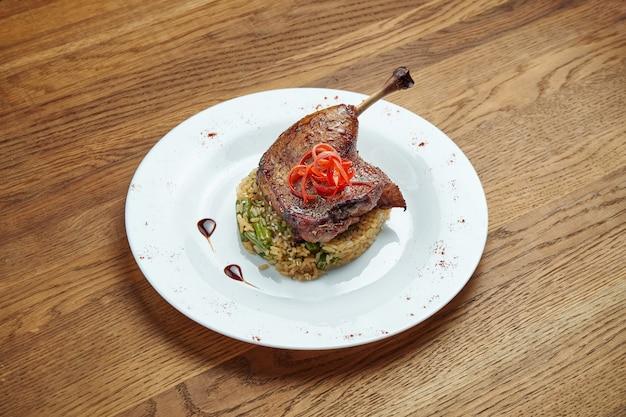 Apetyczna kaczki noga z ryżem z szparagami w białym talerzu na drewnianym tle. danie zdrowej diety. ścieśniać