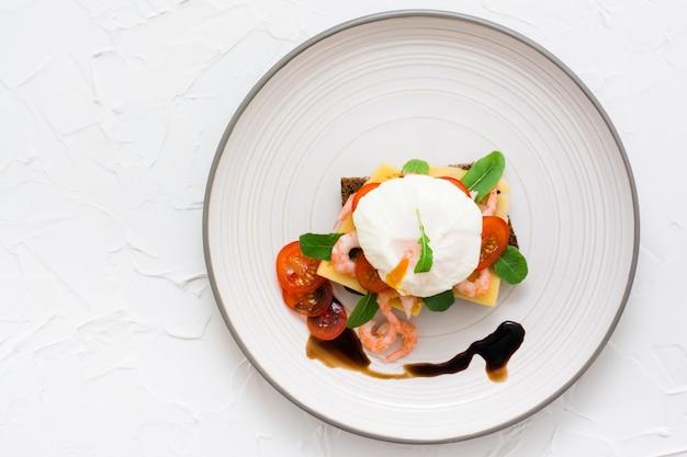 Apetyczna kanapka z jajkiem w koszulce, pomidorem, krewetkami i rukolą na talerzu. widok z góry