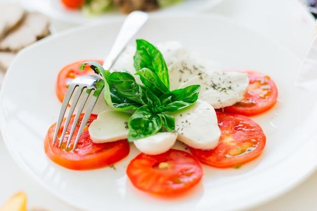 Apetyczna mozzarella i pokrojone pomidory na talerzu widelcem. przyjęcie. ścieśniać.