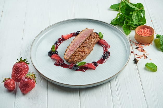 Apetyczna pieczona pierś z kaczki z owocami w ceramicznym talerzu na białym drewnianym tle w kompozycji ze składnikami. obsługa restauracji
