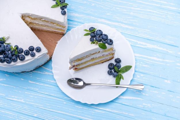 Apetyczna poduszka biszkoptowa do sernika ozdobiona biało-kremowymi jagodami i miętą stoi na drewnianym stole w stylu rustykalnym, niebieskim. słodkie ciasto z kawałkiem i łyżką na talerzu