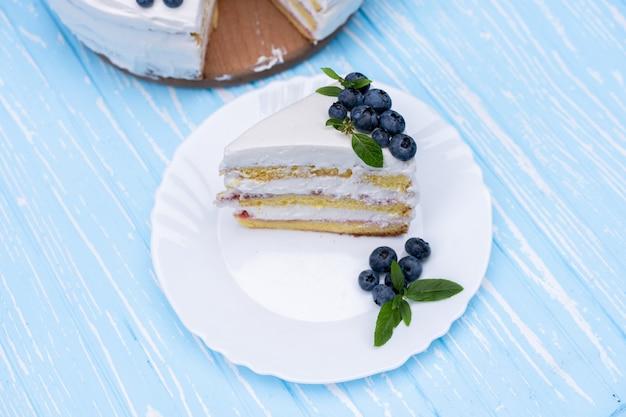 Apetyczna poduszka na herbatniki z sernikiem ozdobiona białymi kremowymi jagodami i miętowymi stojakami na drewnianym niebieskim rustykalnym stole. słodkie ciasto z kawałkiem i łyżką na talerzu