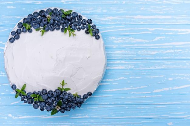 Apetyczna poduszka pod biszkopt z sernikiem ozdobiona białymi kremowymi jagodami i miętowymi stojakami na drewnianym niebieskim niebieskim stole. słodkie ciasto z kawałkiem na talerzu
