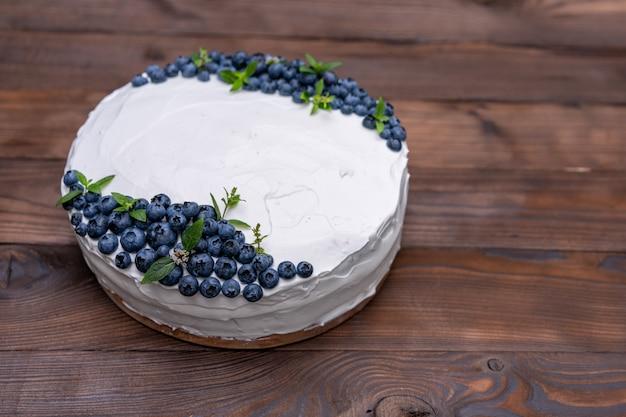 Apetyczna poduszka pod biszkopt z sernikiem ozdobiona białymi kremowymi jagodami i miętowymi stojakami na drewnianym rustykalnym stole. słodkie ciasto z kawałkiem na talerzu