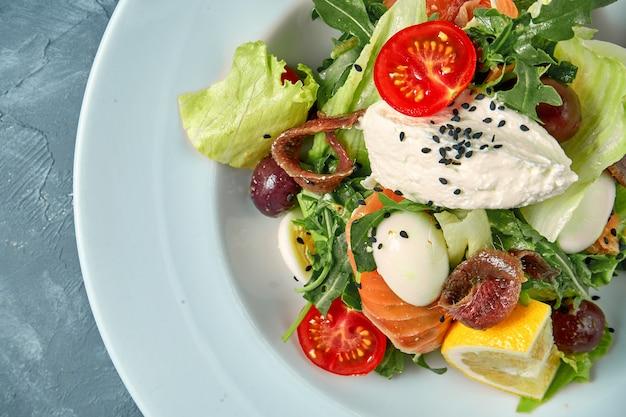Apetyczna sałatka z pomidorami, łososiem, anchois i twarożkiem w białym talerzu na betonie