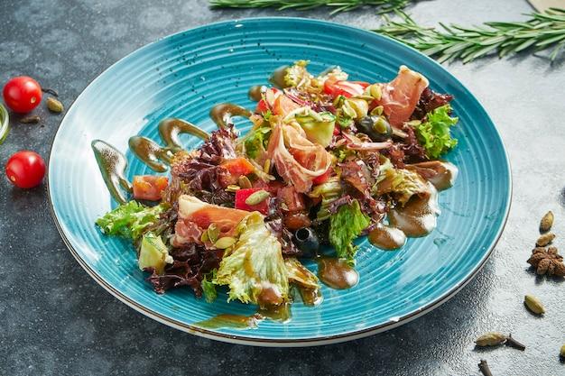 Apetyczna sałatka z szynką parmeńską, sałatą, oliwkami i słodkim sosem na niebieskim talerzu ceramicznym na ciemnej powierzchni. zamknąć widok