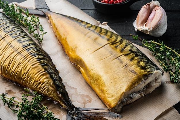 Apetyczna wędzona makrela rybna, na czarnym drewnianym stole w tle
