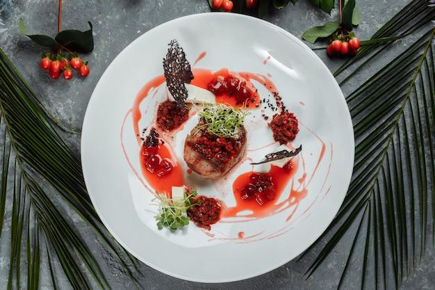 Apetyczna wołowina w słodkim sosie z bliska. siekane mięso wołowe w sosie wiśniowym z warzywami na talerzu. pyszna kuchnia europejska