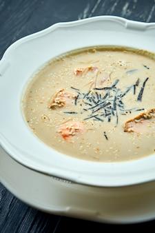 Apetyczna zupa kokosowa z łososiem, nori i sezamem, podawana w białym talerzu na stole z ciemnego drewna