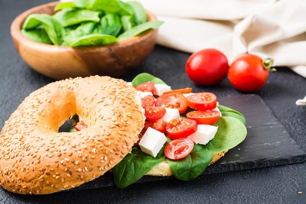 Apetyczne bajgle faszerowane pomidorami, fetą i liśćmi szpinaku na łupkowej desce na czarnym tle. lekka zdrowa przekąska. zbliżenie