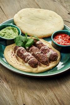 Apetyczne bułki kebabu lyulya - ugotowane na mięsie jagnięcym z dodatkiem hummusa z pita i salsą na talerzu ceramicznym. pionowy, drewniany stół, kuchnia wschodnia