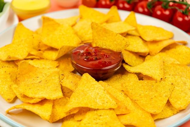 Apetyczne chipsy nachos na białym talerzu i pikantny sos na pyszny warzywny posiłek.