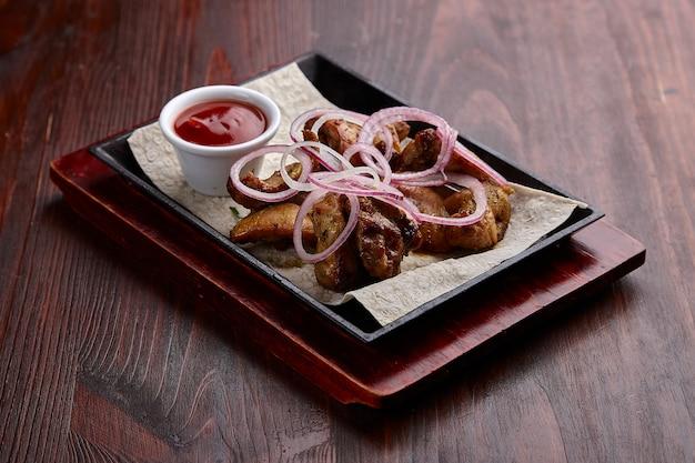 Apetyczne dania z grilla z sosem na ciemnym drewnianym stole.