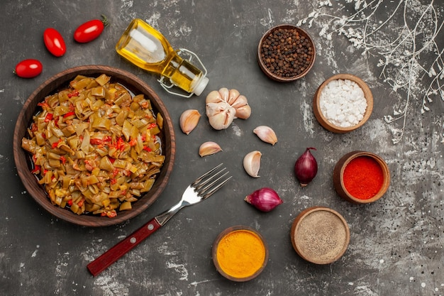 Apetyczne danie fasolka szparagowa i pomidory obok widelca butelka oleju czosnek cebula pomidory i miski kolorowych przypraw na ciemnym stole