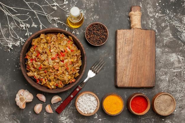 Apetyczne danie fasolka szparagowa na talerzu obok widelca drewniana deska do krojenia czosnek butelka oleju i miski przypraw na ciemnym stole