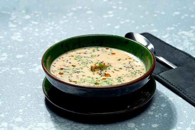 Apetyczne danie kuchni panazjatyckiej - serowa zupa miso w zielonej misce na szarej powierzchni