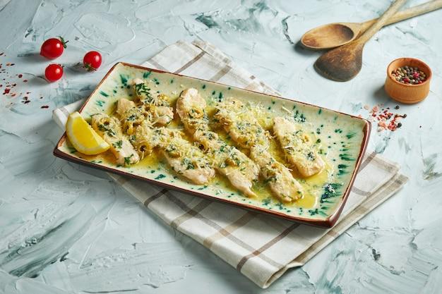Apetyczne danie kuchni włoskiej - indyk piccata z parmezanem i oliwkami w białym talerzu na szarym stole. ścieśniać