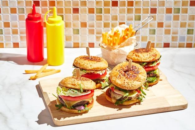 Apetyczne domowe hamburgery na drewnianej desce do krojenia z jasnym światłem słonecznym burger z kotletami cielęcymi ser pamidorom czerwona cebula sałata rukola i frytki koncepcja fast food