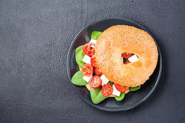Apetyczne gotowe do spożycia bajgle nadziewane pomidorami, fetą i liśćmi szpinaku na talerzu na czarnym tle. lekka zdrowa przekąska. widok z góry. skopiuj miejsce