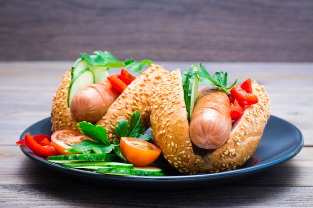 Apetyczne hot dogi ze smażonych kiełbas, bułek sezamowych i świeżych warzyw na talerzu na drewnianym stole