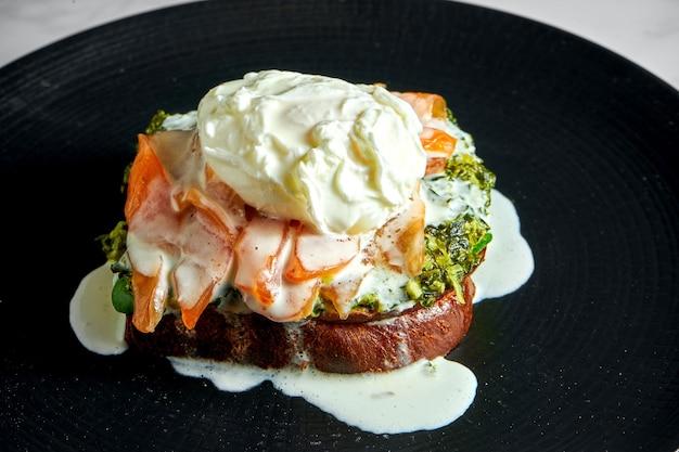 Apetyczne i zdrowe śniadanie - tosty z łososiem, kremowym szpinakiem i jajkiem w koszulce, podane na czarnym talerzu na marmurowej powierzchni