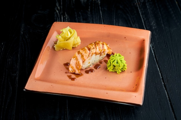 Apetyczne japońskie nigiri z wędzonym łososiem i sosem unagi podane na talerzu z imbirem i wasabi na czarnym drewnianym tle
