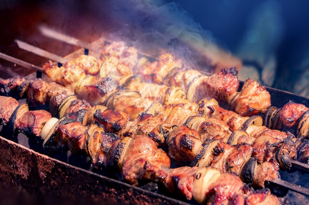 Apetyczne kawałki marynowanego mięsa, cebuli i warzyw są naciągane na szaszłyki i gotowane na grillach węglowych w aromatycznym gorącym dymie. zbliżenie