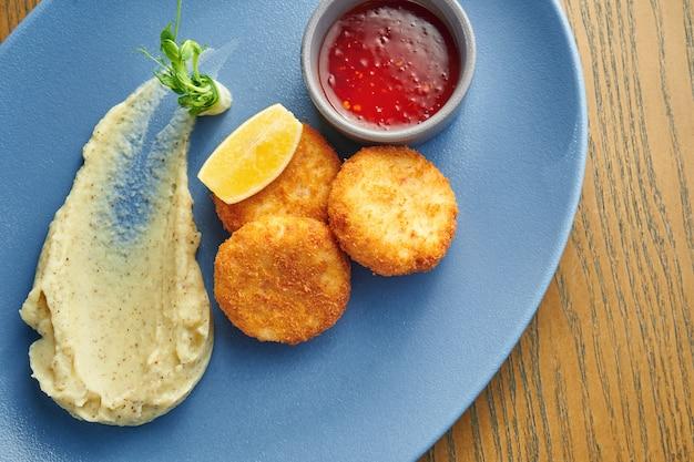 Apetyczne krokiety z kurczaka panierowane w czerwonym sosie i puree ziemniaczane na niebieskim talerzu z pikantnym czerwonym sosem. drewniana ściana