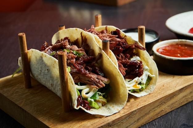 Apetyczne meksykańskie tacos z wołowiną, kapustą, cebulą i natką pietruszki w specjalnych stojakach. tradycyjna kuchnia meksykańska