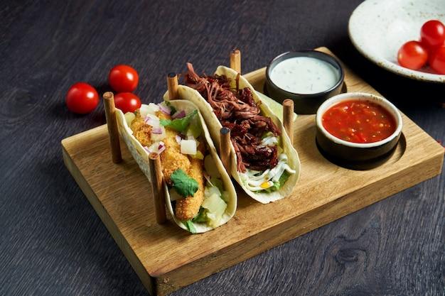 Apetyczne meksykańskie tacos ze smażonym kurczakiem i duszoną wołowiną, kapustą, cebulą i natką pietruszki w specjalnych stojakach. tradycyjna kuchnia meksykańska