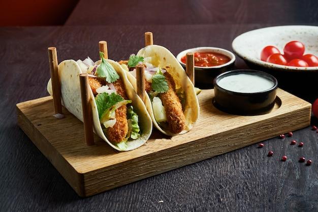 Apetyczne meksykańskie tacos ze smażonym kurczakiem, kapustą, cebulą i natką pietruszki w specjalnych stojakach. tradycyjna kuchnia meksykańska