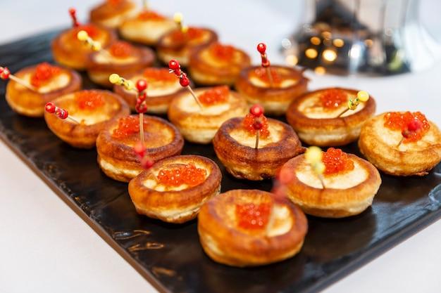 Apetyczne przekąski na stole w formie bufetu na imprezie. kanapki z czerwonym kawiorem. zbliżenie.