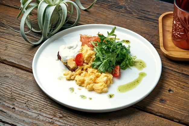 Apetyczne śniadanie - jajecznica z rukolą, łososiem i tostem z greckim jogurtem na talerzu na drewnianym stole