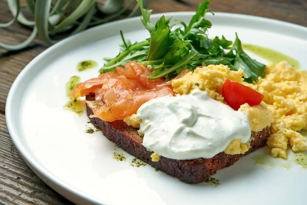 Apetyczne śniadanie - jajecznica z rukolą, łososiem i tostem z greckim jogurtem na talerzu na drewnianym