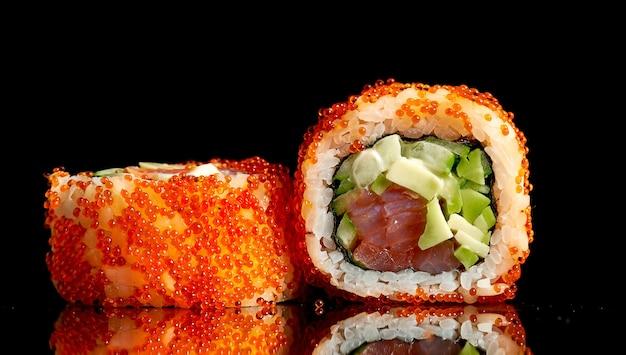 Apetyczne sushi california w kawiorze tobiko z tuńczykiem i awokado na ciemnym tle. zbliżenie, selektywne skupienie