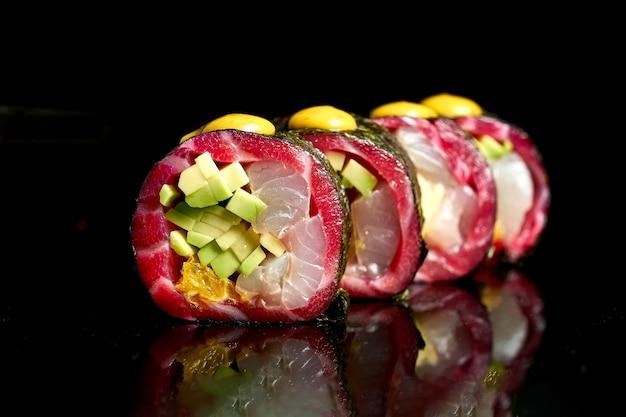 Apetyczne sushi z różnymi rodzajami ryb: łososiem gravlax, tuńczykiem i awokado na ciemnym tle. zbliżenie, selektywne skupienie