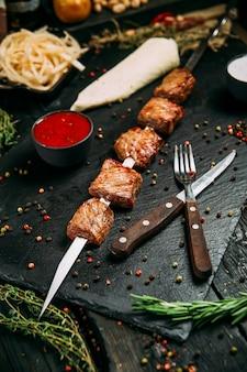 Apetyczne szaszłyki z baraniny z czerwonym sosem i marynowaną cebulą na czarnej desce