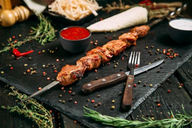 Apetyczne szaszłyki z kaczki z czerwonym sosem i marynowaną cebulą na czarnej desce