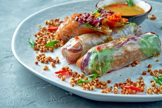 Apetyczne wegetariańskie sajgonki z warzywami i ostrym sosem na białym talerzu