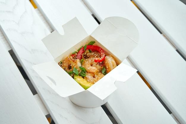 Apetyczny azjatycki makaron woka z warzywami, cebulą, sosami i krewetkami w białym pudełku na białym drewnianym talerzu