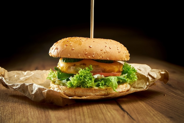 Apetyczny burger z kurczakiem, sałatą, topionym serem, ogórkiem i pomidorem, podawany na papierze, na drewnianej powierzchni. burger z kurczaka