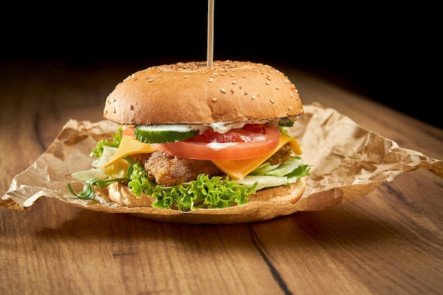Apetyczny burger z rybą, serem, sałatą, pomidorami i ogórkami na papierze na drewnianej powierzchni. burger rybny