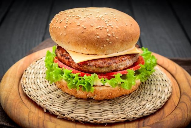 Apetyczny cheeseburger z pomidorami na drewnianym tle