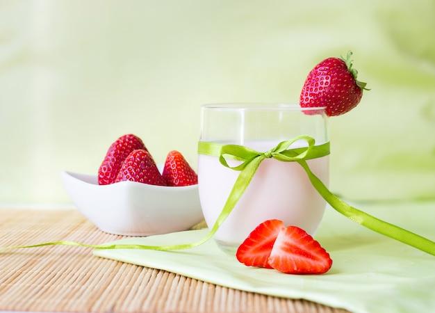 Apetyczny domowy koktajl truskawkowy w szkle z dekoracją kokardki i truskawki