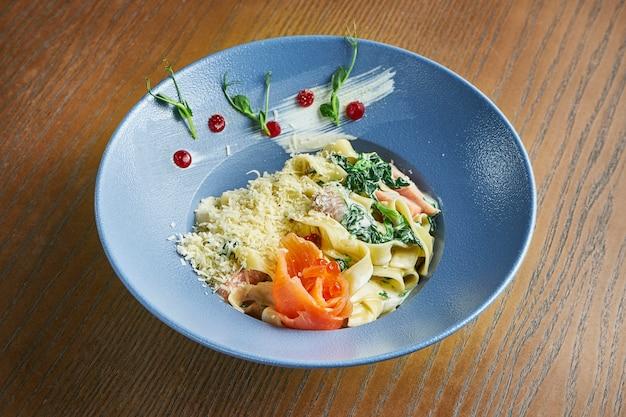 Apetyczny, domowy makaron tagliatelle ze szpinakiem i łososiem, parmezanem w niebieskiej misce na drewnianej powierzchni. kuchnia włoska. dodaj hałas na post. selektywne ustawianie ostrości