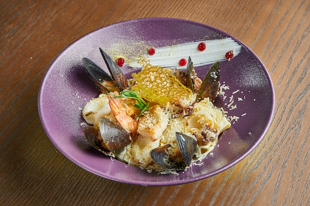 Apetyczny domowy tagliatelli z małżami, krewetkami i kałamarnicą, parmezanem w misce na drewnianej powierzchni. dodaj hałas na post. kuchnia włoska